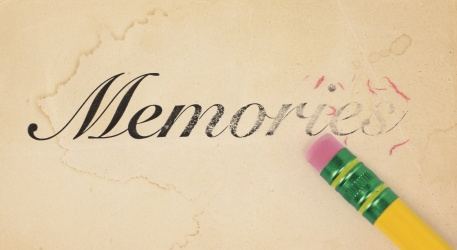 Close up of a yellow pencil erasing the word, 'memories' from old, yellowed paper